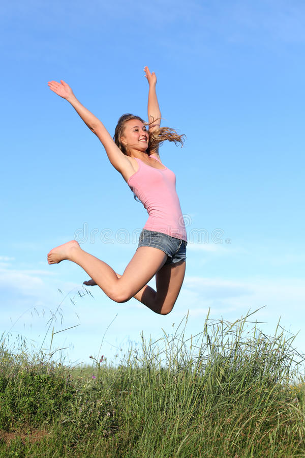 Blonde teenager girl jumping happy in the mountain. With the blue sky in the background stock image