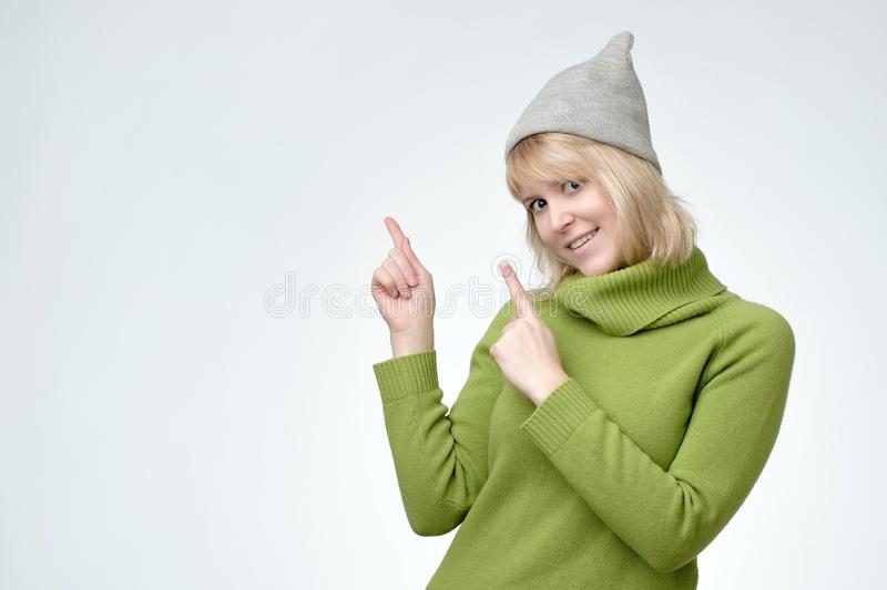 Blonde teenager woman is very happy pointing with hand and finger to the side stock image