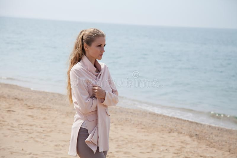 Blonde thoughtfully walks on sandy beach sea shore royalty free stock images