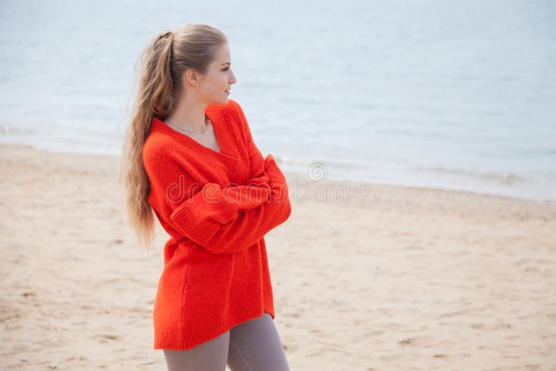 Blonde thoughtfully walks on sandy beach sea shore stock image