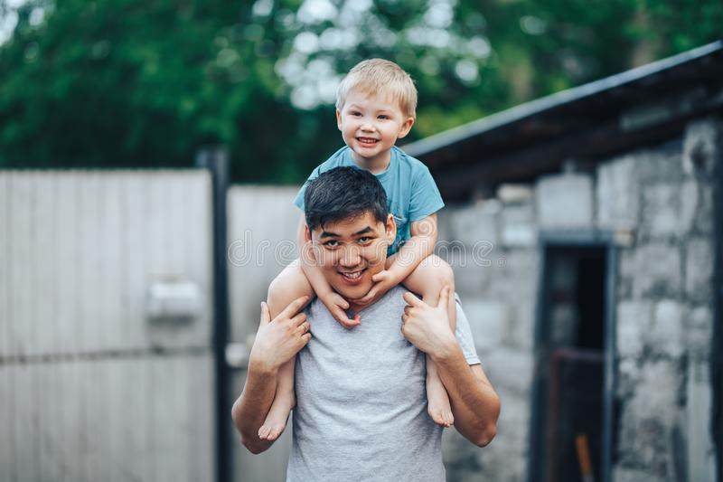 Blonde three years old boy sitting on father`s shoulders. Kazakh father and caucasian mother. Happy father with black hair play royalty free stock image