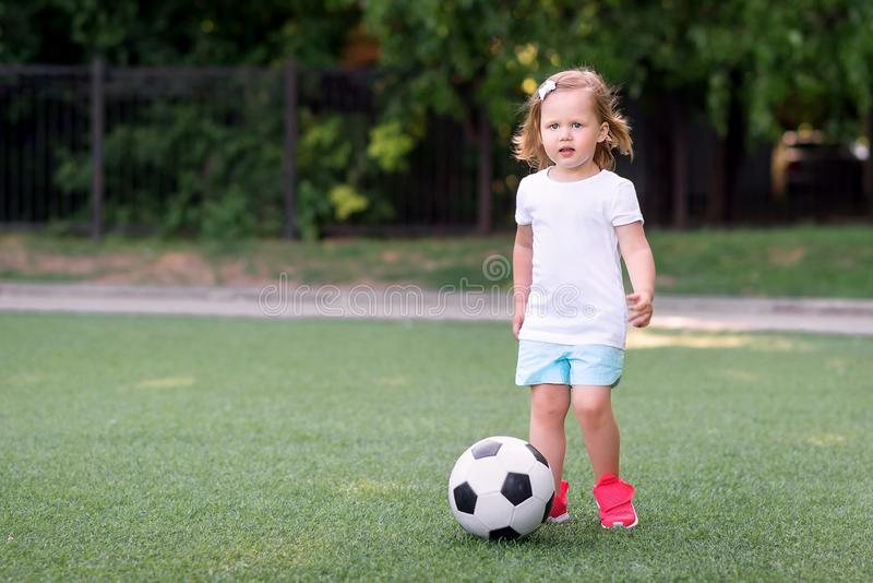Blonde toddler girl in blue shorts and pink sneakers playing with soccer ball at football field or stadium outdoors. Girl power stock photos