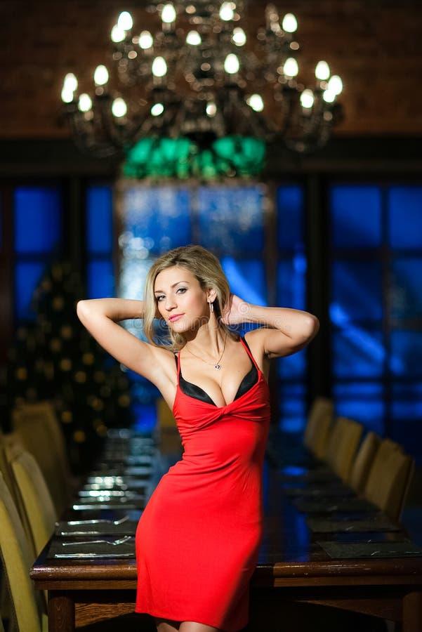 Blonde très belle et sexy de fille avec le buste luxuriant dans dres rouges images stock