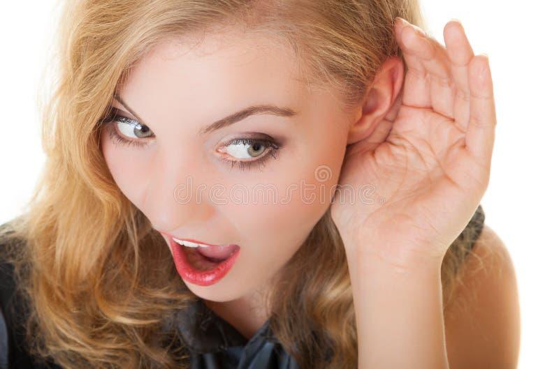 Blonde verrast roddelmeisje met hand achter oor het luisteren geheim stock foto's