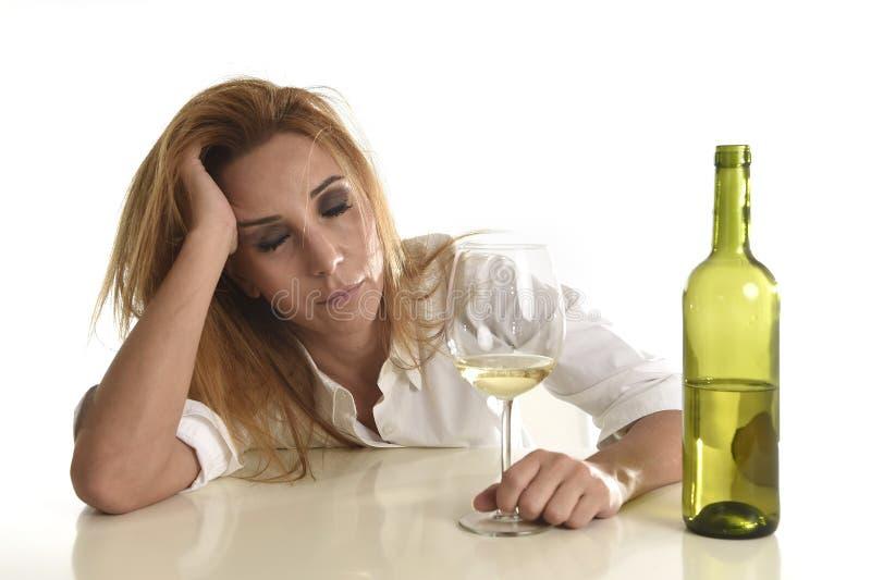 Blonde verspilde en gedeprimeerde alcoholische gedronken vrouw die witte wanhopige droevig van het wijnglas drinken stock foto's
