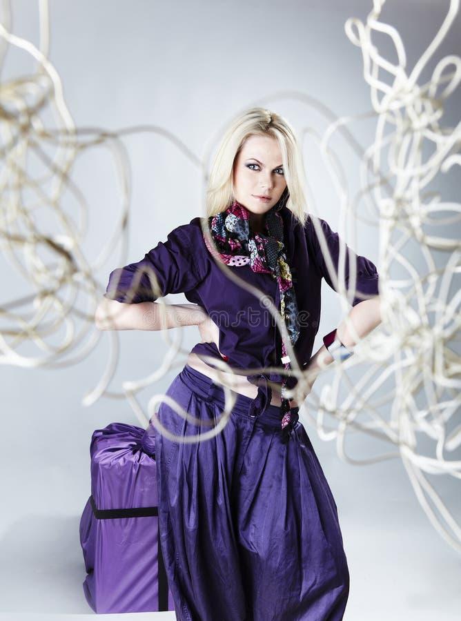 Blonde in viooltje op een grijze achtergrond. royalty-vrije stock afbeelding
