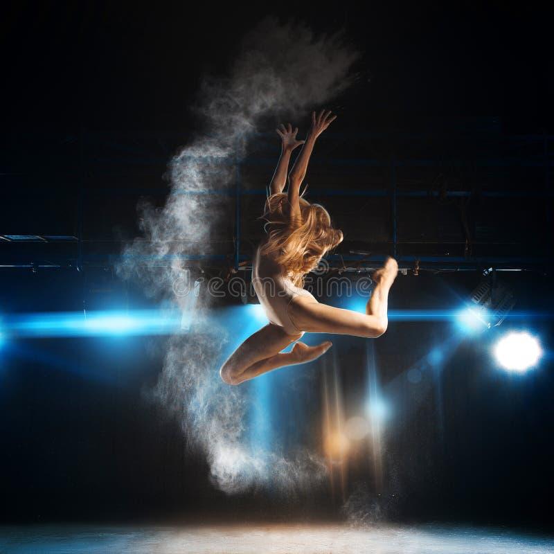 Blonde volwassen ballerina in sprong op stadium van theater royalty-vrije stock foto