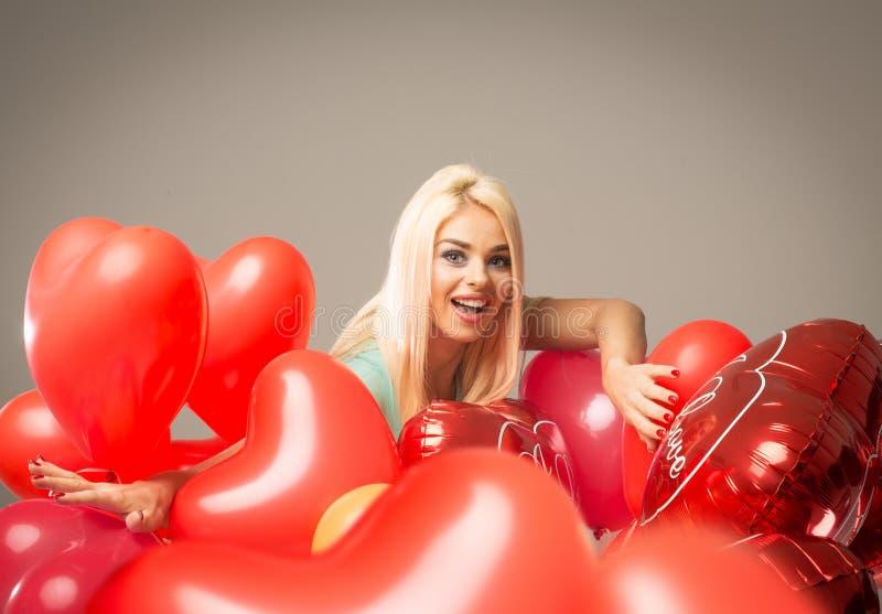 Blonde vrolijke vrouw met rood ballonshart stock afbeeldingen