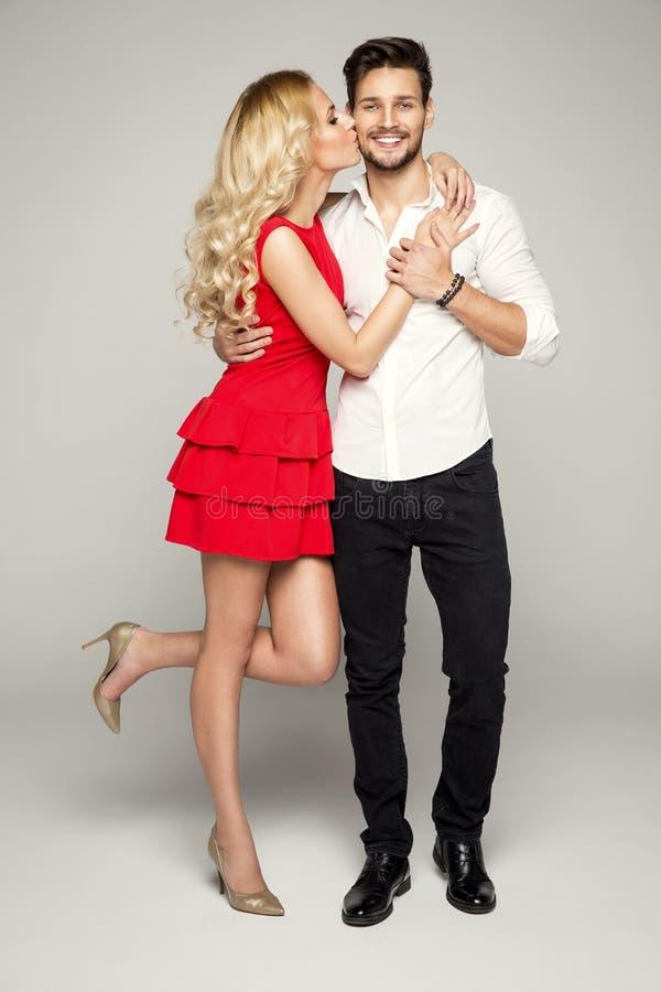 Blonde vrouw die de jonge mens kussen stock foto