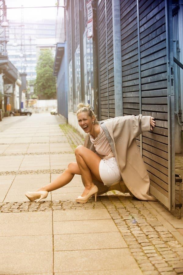 Blonde vrouw die in de straat lachen stock afbeeldingen