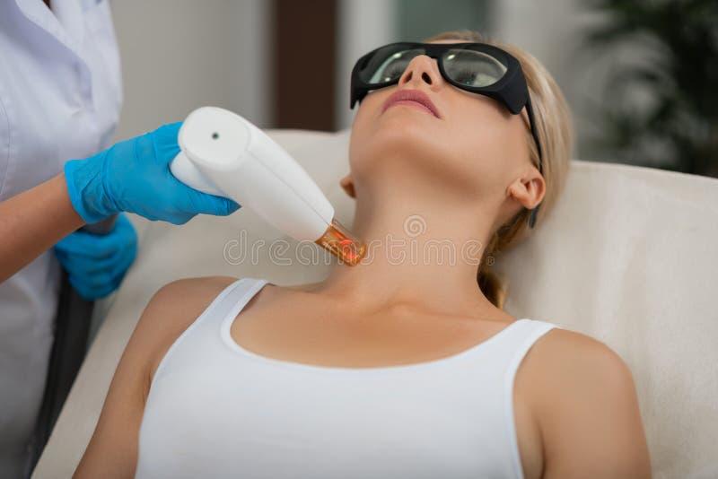 Blonde vrouw die haar de huidbehandeling krijgen van de laserhals stock foto's