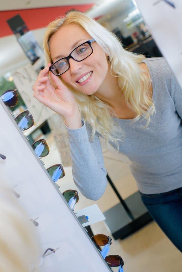 Blonde vrouw die oogglazen in opticienopslag dragen stock foto