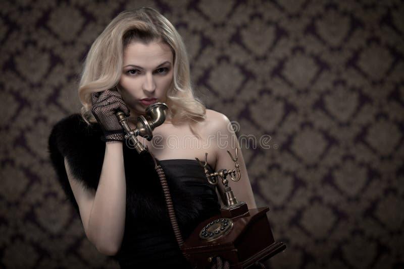 Blonde vrouw die op de retro telefoon spreken stock foto