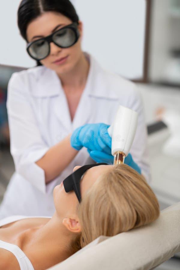 Blonde vrouw die op een laag liggen die gezichtsbehandeling krijgen royalty-vrije stock afbeelding