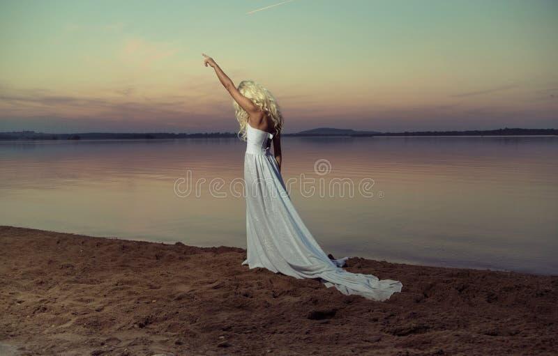 Blonde vrouw die op het strand loopt stock afbeelding