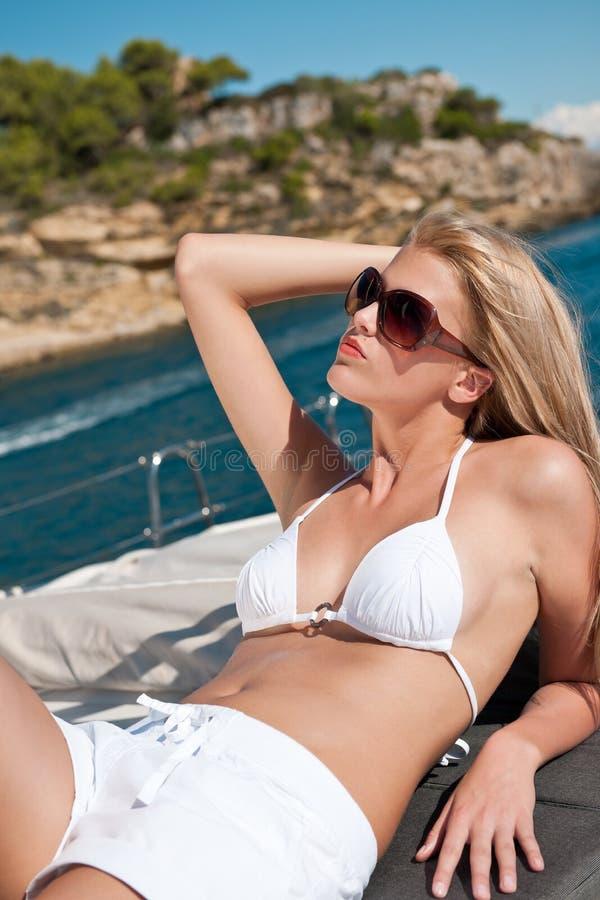 Blonde vrouw die op luxejacht zonnebaadt met bikini stock afbeelding