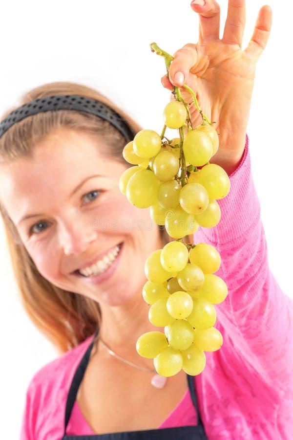 Blonde vrouw die rijpe druiven, witte achtergrond houden stock foto's