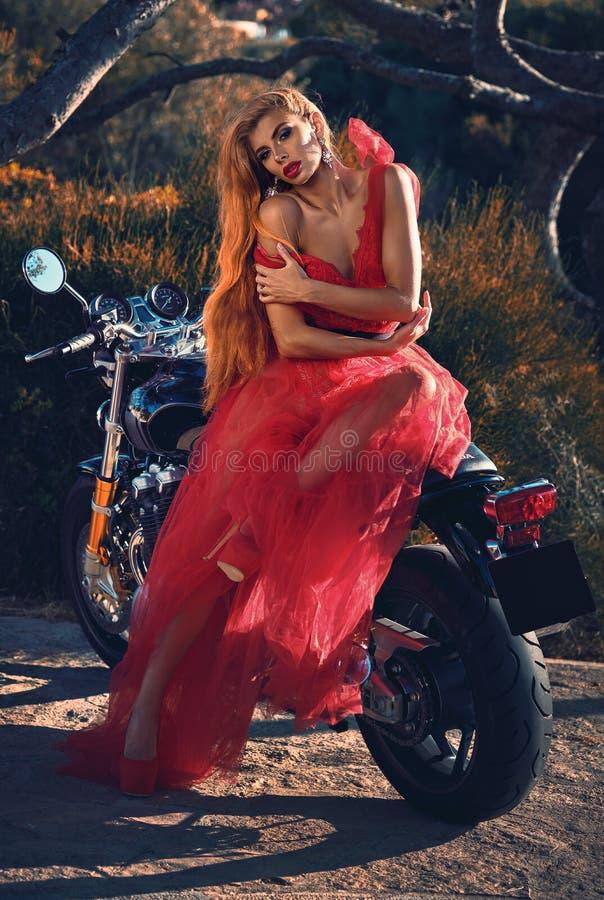 Blonde vrouw die rode pluizige kledingszitting op motorfiets dragen die in openlucht op aard stellen die camera bekijken royalty-vrije stock foto's