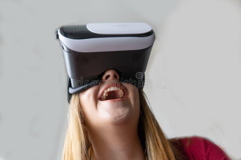 Blonde vrouw die speelt en lacht, met een bril voor virtuele realiteit Uitstekend, geniet van het bekijken met de fictie van de t stock foto