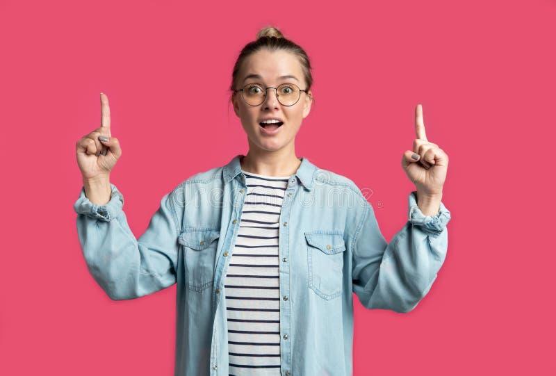 Blonde vrouw die vingers tot exemplaarruimte richten die, over roze achtergrond wordt geïsoleerd royalty-vrije stock foto