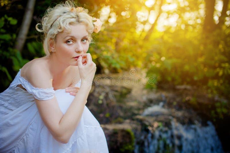 Blonde vrouw die witte kleding draagt stock afbeelding