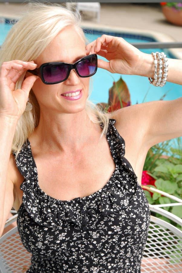 Blonde vrouw door de pool stock fotografie