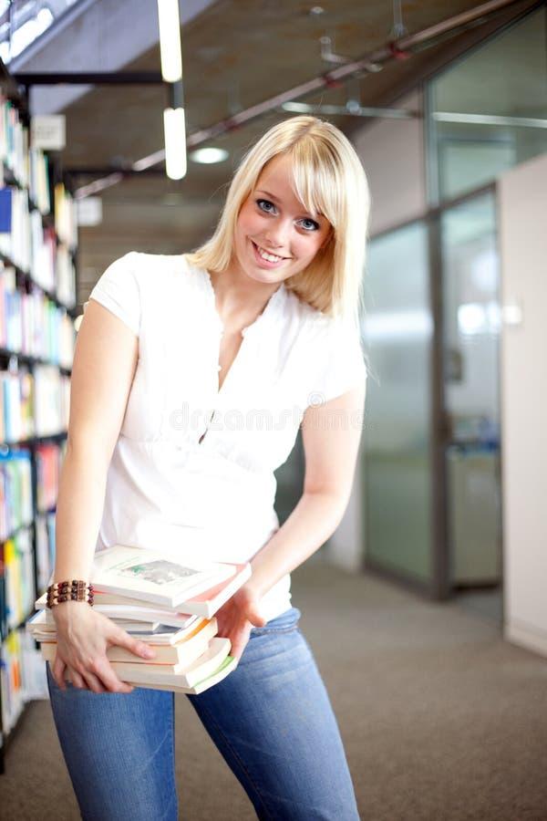 Blonde vrouw in een bibliotheek royalty-vrije stock foto's