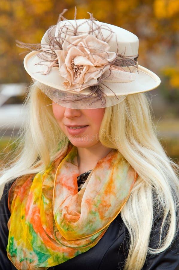 Blonde vrouw in een elegante hoed stock afbeeldingen