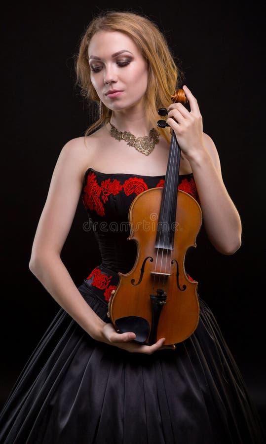 Blonde vrouw in grote kleding met viool royalty-vrije stock foto's