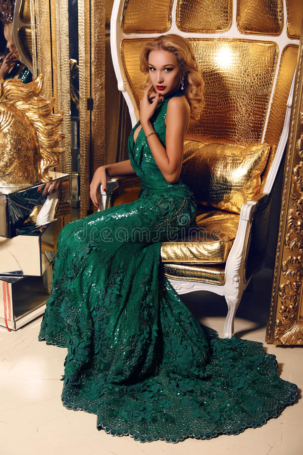 Blonde vrouw in het elegante lovertjekleding stellen in luxueuze binnenlands stock foto's