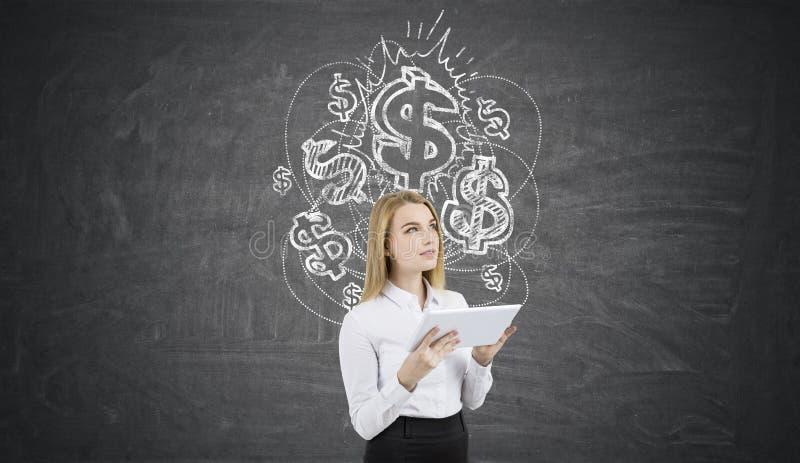 Blonde vrouw met een tablet dichtbij bord met dollartekens stock foto's