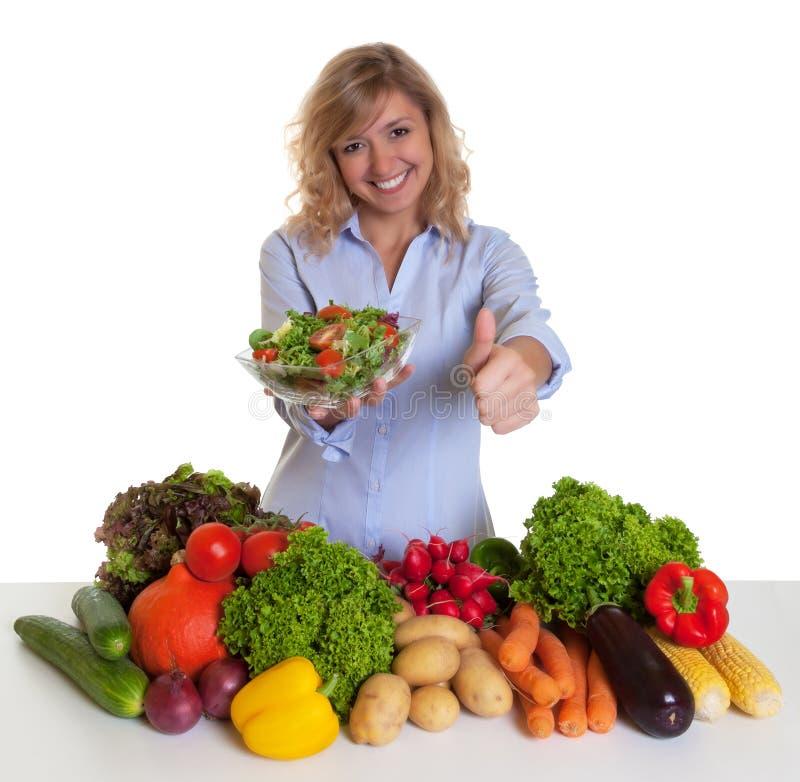 Blonde vrouw met groenten en groene salade die duim tonen stock afbeeldingen