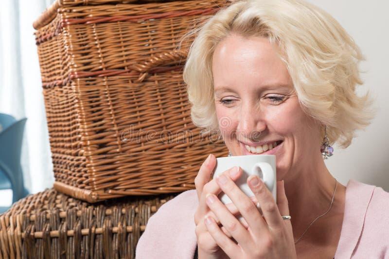 Blonde Vrouw met Hete Drankglimlachen aan zich stock afbeelding