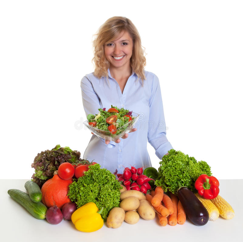 Blonde vrouw met verse groenten die verse salade aanbieden stock fotografie
