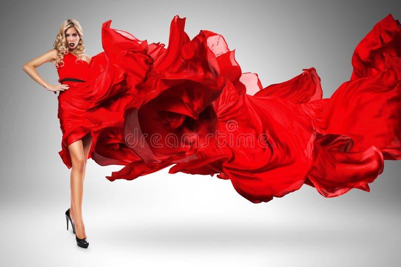 Blonde vrouw in mooie geblazen rode kleding stock foto's
