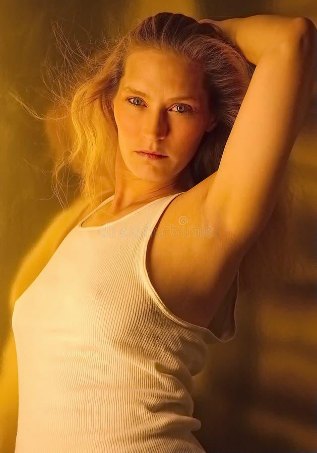 Blonde vrouw in mouwloos onderhemd stock foto