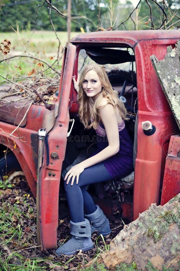 Blonde vrouw in oude vrachtwagen stock foto