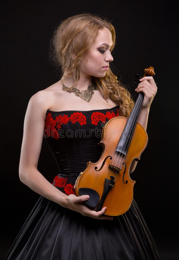 Blonde vrouw in overlegkleding met viool stock fotografie
