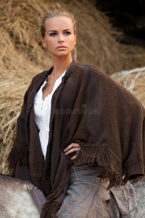 Blonde vrouw in poncho stock afbeeldingen