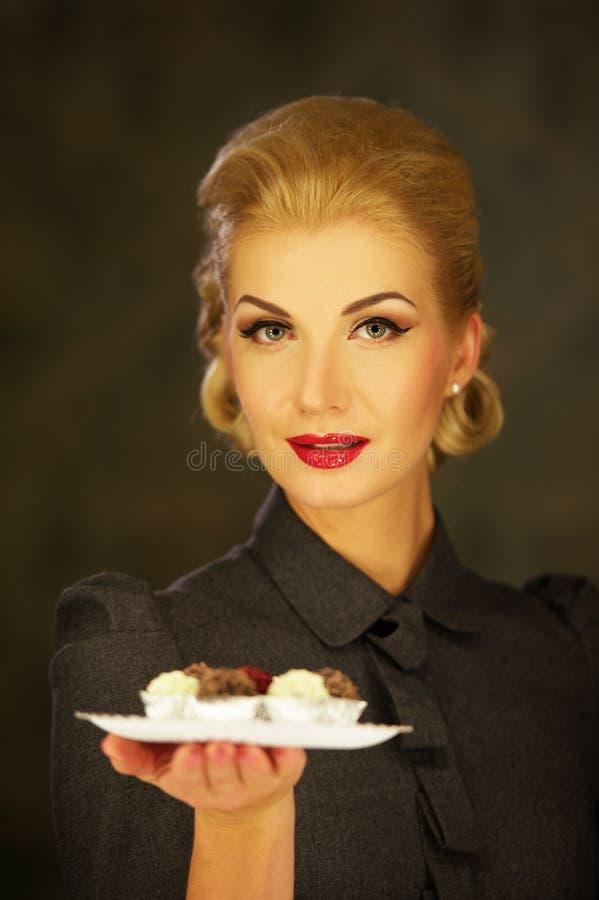 Blonde vrouw in retro kleding met plaat van snoepjes stock foto's