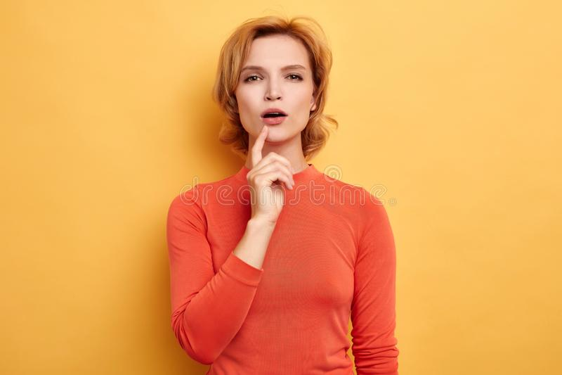 Blonde vrouw wat betreft haar kin met twijfelachtige en sceptische uitdrukking, royalty-vrije stock afbeelding