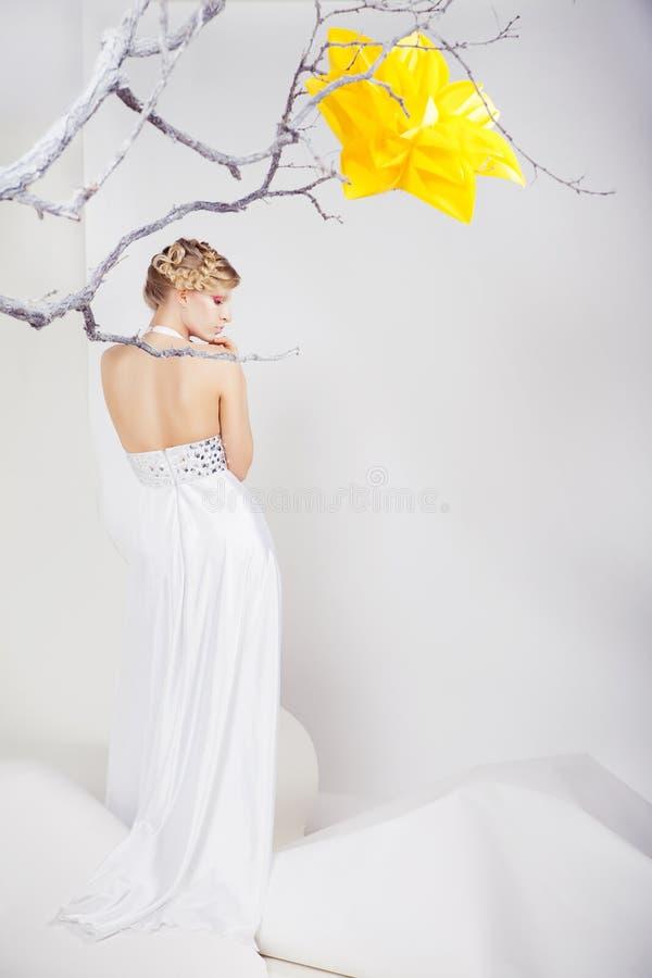 Blonde vrouw in witte kleding met grote gele bloem royalty-vrije stock afbeelding