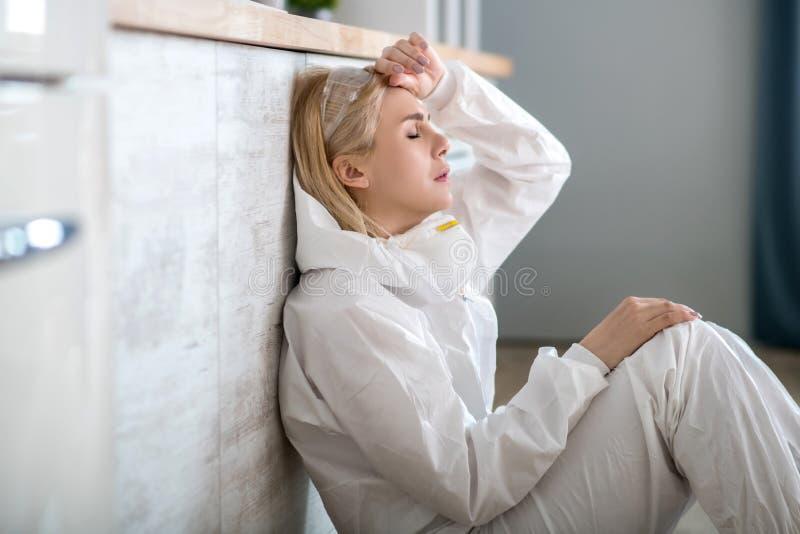 Blonde vrouw in witte werkkleding die op de vloer zit, voelt zich moe royalty-vrije stock foto's