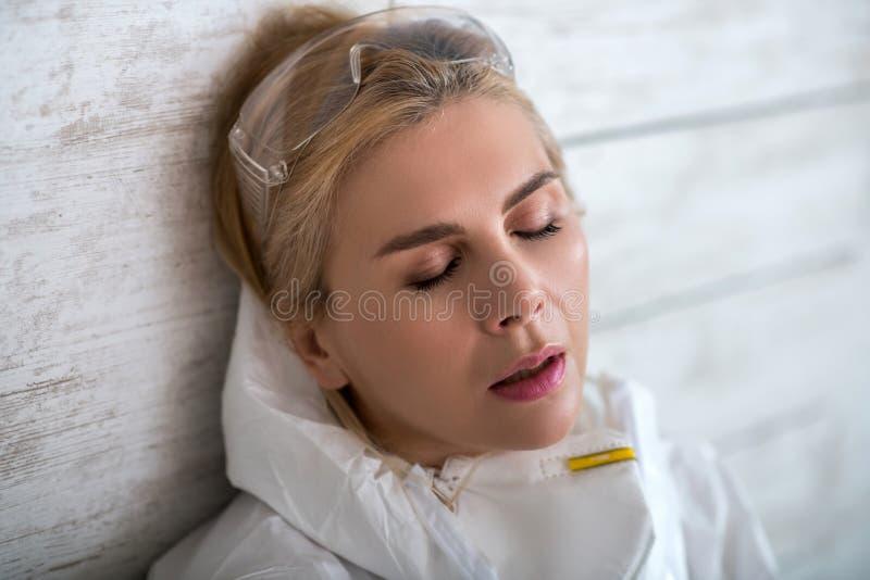 Blonde vrouw in witte werkkleding met hoofdpijn stock afbeelding