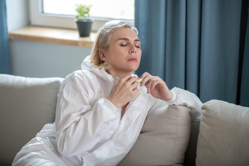Blonde vrouw in witte werkkleding op de sofa royalty-vrije stock afbeeldingen