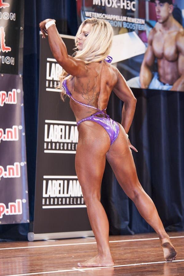 Blonde vrouwelijke bodybuilder in roze bikini op stadium stock afbeeldingen