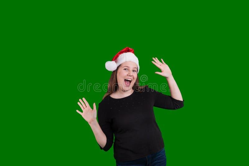 Blonde vrouwelijke handen die omhoog de opgewekte uitdrukking van Kerstmissanta claus hoed dragen royalty-vrije stock foto