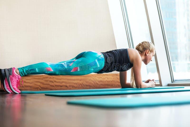 Blonde vrouwelijke het doen plank statische oefening in gymnastiek stock fotografie
