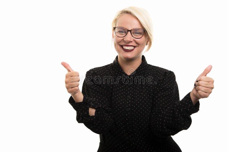 Blonde vrouwelijke leraar die glazen dragen die dubbele duim op Duitsland tonen stock fotografie