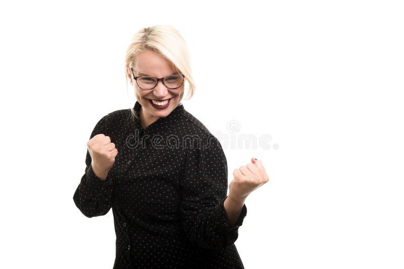 Blonde vrouwelijke leraar die glazen dragen die dubbele vuist tonen gestur stock foto